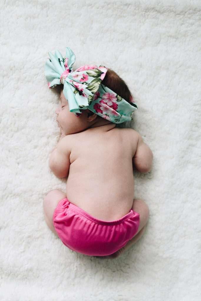 Slika novorojenčka na mehki podlagi z veliko pisano pentljo na glavi.