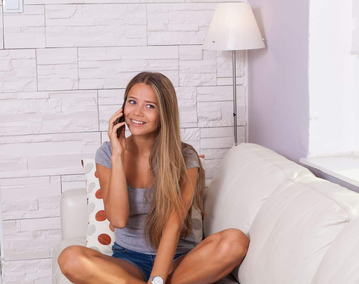 woman in gray scoop-neck top talking on smartphone