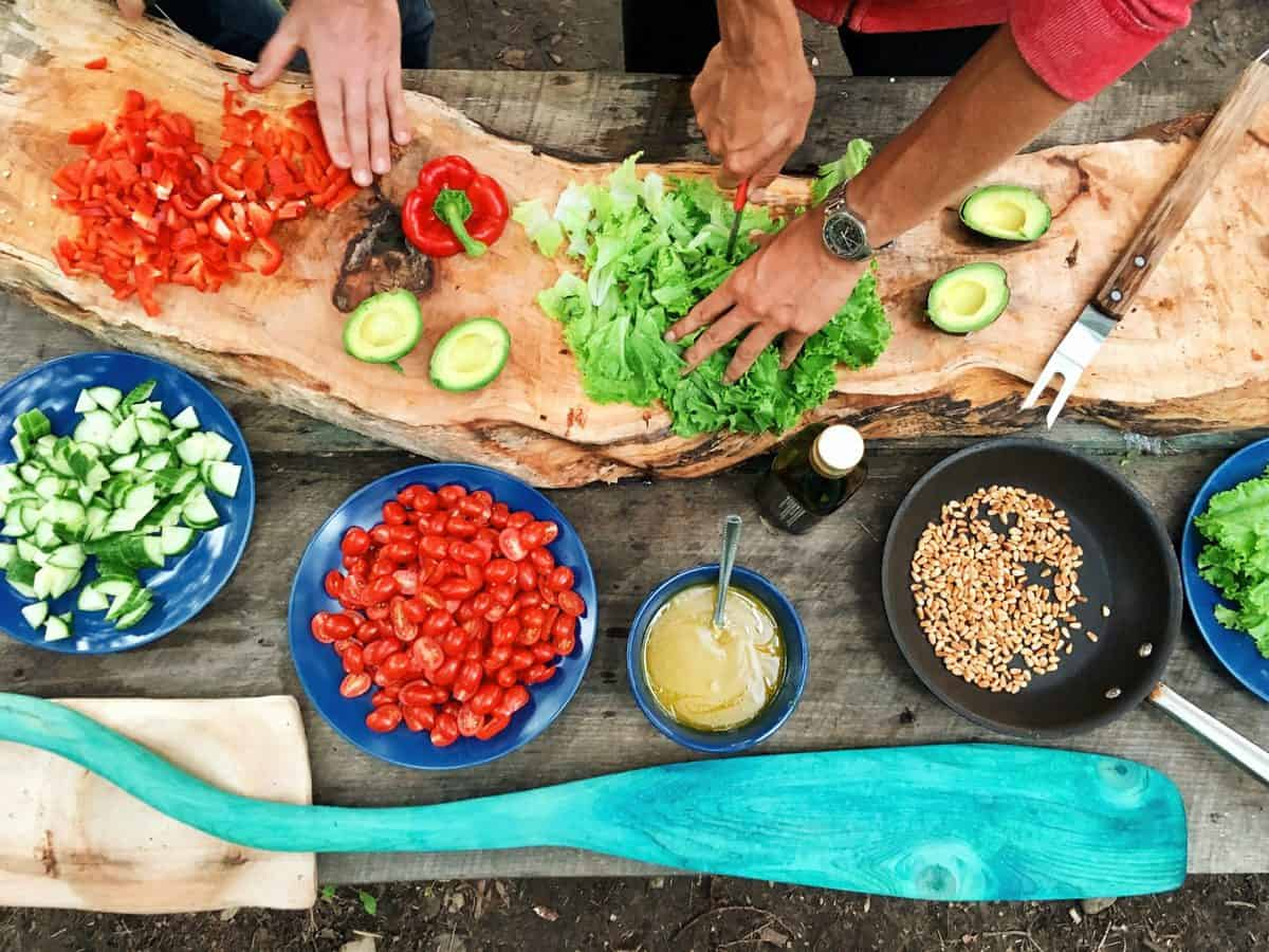 person slicing green vegetable in front of round ceramic plates with assorted sliced vegetables during daytime